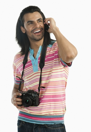 Photographer holding a digital camera and talking on a mobile phone Foto de archivo