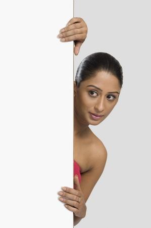 Woman peeking from behind a door Stock Photo - 10168729