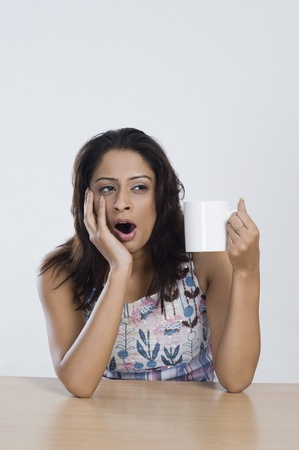 Woman holding a cup of coffee and yawning Stock Photo - 10168110