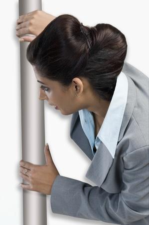behind: Woman peeking from behind a door LANG_EVOIMAGES