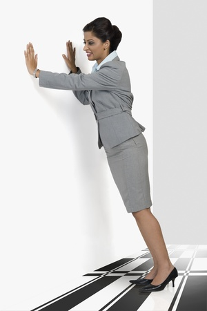 gurgaon: Businesswoman stretching against a wall LANG_EVOIMAGES