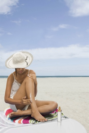 Woman applying suntan lotion on the beach Stock Photo - 10167066
