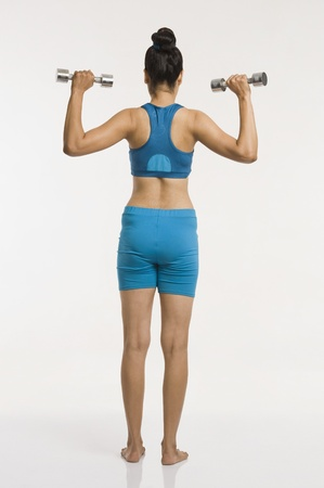 Rear view of a woman exercising with dumbbells