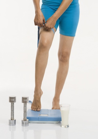Woman standing on a weight scale and measuring her thigh Stock Photo - 10168622