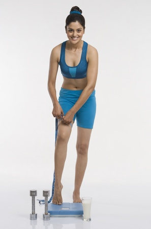 Woman standing on a weight scale and measuring her thigh Stock Photo - 10167012