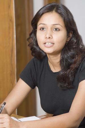 mujeres sentadas: Mujer que estudia en una habitaci�n