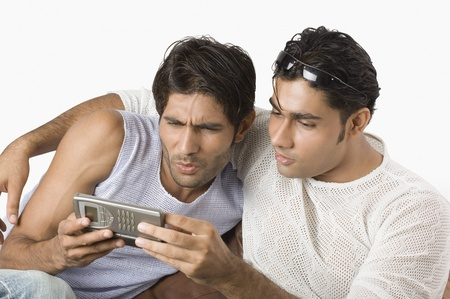 Two friends text messaging on a mobile phone photo