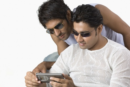 telecommunicating: Two friends text messaging on a mobile phone