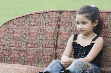 elementary age girls: Girl sitting on a couch
