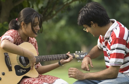Woman playing guitar with her boyfriend in a park