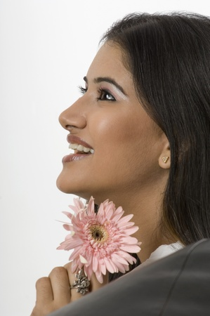 Close-up of a woman smiling and holding a flower photo