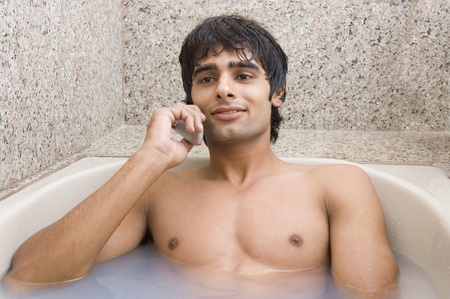 and the horizontal man: Man relaxing in the bathtub and talking on a mobile phone Stock Photo