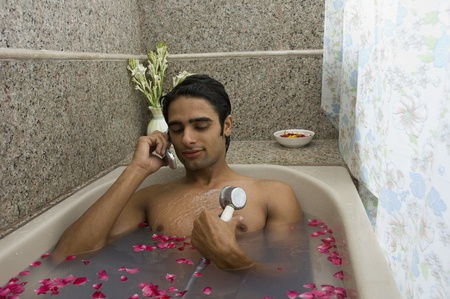 Man taking a shower and talking on a mobile phone photo