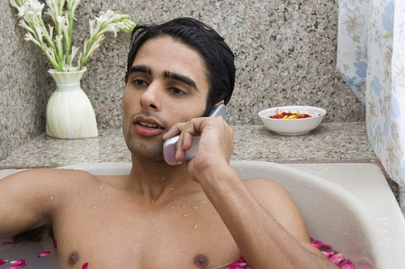 bathing man: Man relaxing in the bathtub and talking on a mobile phone Stock Photo