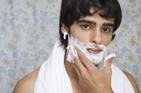 Man applying shaving cream on his face