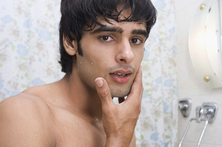 body grooming: Portrait of a man touching his face after shave