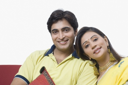 indian couple: Couple sitting on a couch and smiling Stock Photo