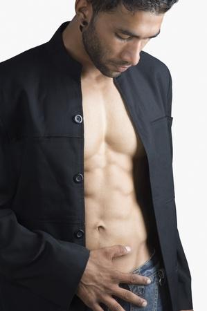 muscle shirt: Primer plano de un hombre machista comprobar sus m�sculos abdominales