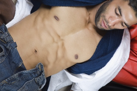 bare chest: Close-up of a macho man lying on bean bags
