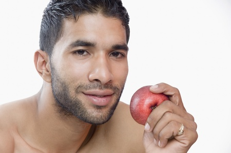 Portrait of a macho man eating apple photo