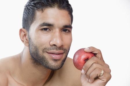 Portrait of a macho man eating apple Standard-Bild