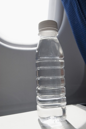 water transportation: Water bottle on seat tray in an airplane, New Delhi, India Stock Photo