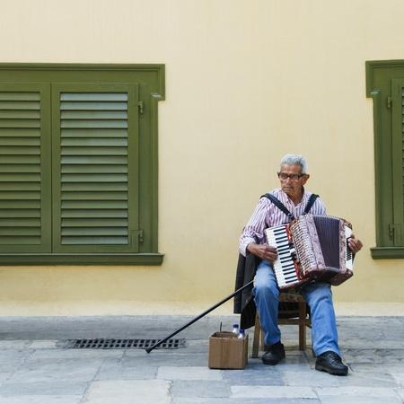 アテネ、ギリシャがアコーディオンを弾いて男