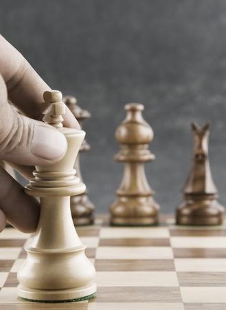 competitividad: La mano del hombre se mueve una pieza rey del ajedrez Foto de archivo