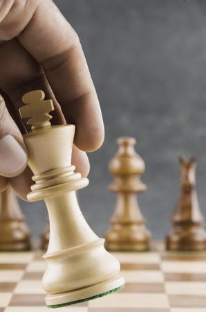 competitividad: Mano humana moviendo un rey pieza de ajedrez