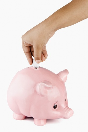 photosindia: Close-up of a persons hand putting a coin into a piggy bank Stock Photo