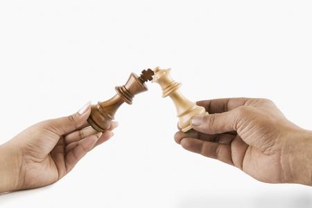 strife: Close-up di un uomo e mani di donna che regge il re e la regina degli scacchi