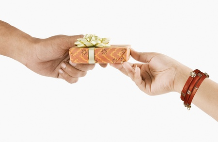 Mans hand giving a gift box to a woman