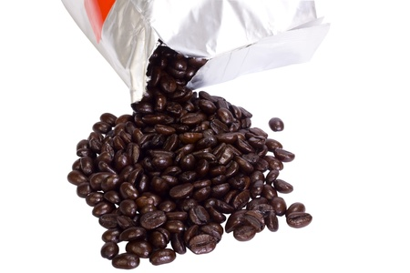 Coffee beans spilling out from a packet Фото со стока