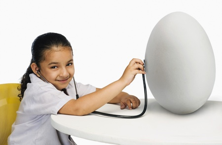 Girl examining a egg with a stethoscope photo