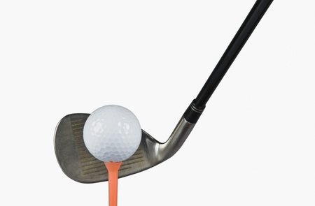 Golf club with a golf ball and a tee