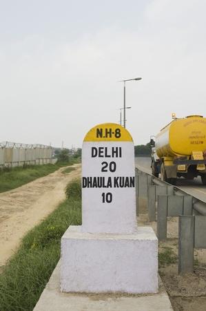 western script: Milestone at the roadside, National Highway 8, New Delhi, India