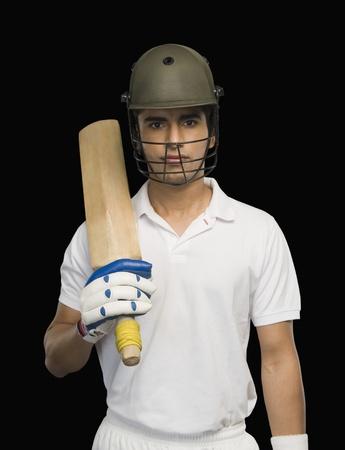 Portrait of a cricket batsman holding a cricket bat photo
