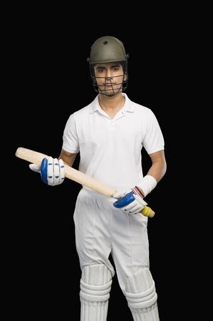 cricket bat: Portrait of a cricket batsman holding a cricket bat Stock Photo
