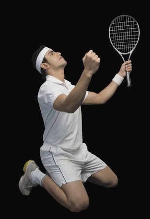 Tennis player celebrating with his arms raised photo