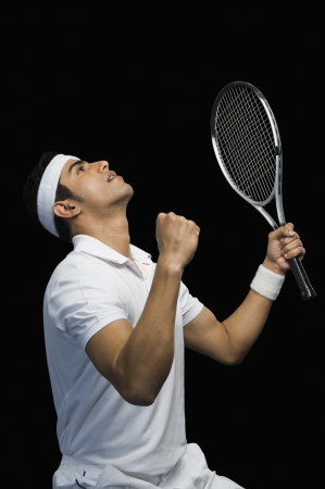 Tennis player celebrating with his arms raised