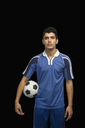 Calciatore che tiene un pallone da calcio Archivio Fotografico - 10239938