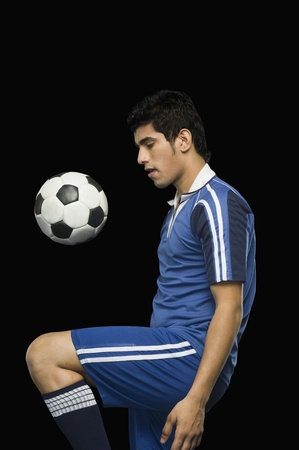 Soccer player practicing with a soccer ball photo