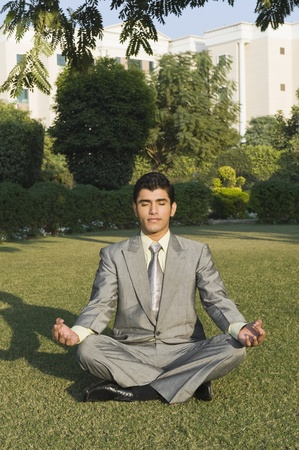 Businessman practicing yoga in a park photo