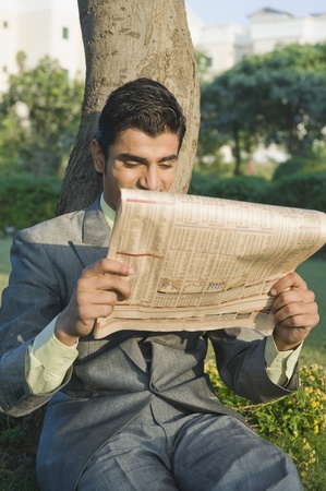 Businessman reading a newspaper in a park photo
