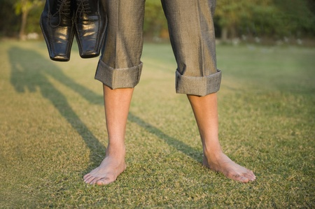 Low section view of a businessman holding shoes in a park