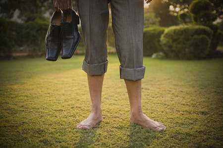 Low section view of a businessman holding shoes in a park photo