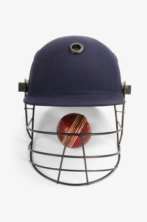 cricket helmet: Close-up of a cricket ball under a cricket helmet
