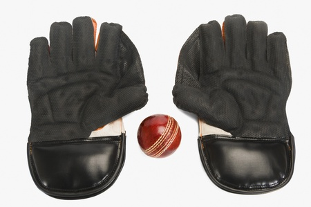手袋を維持する改札のペアを持つクリケット ボールのクローズ アップ 写真素材