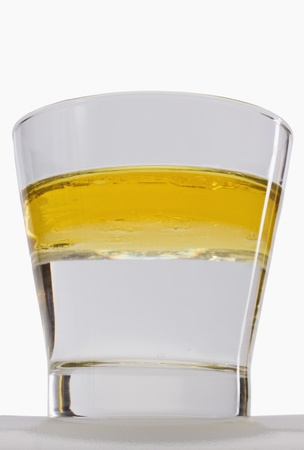 Oil floating on water surface in a glass Standard-Bild