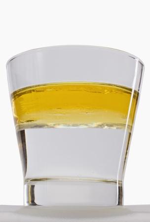 Oil floating on water surface in a glass Foto de archivo